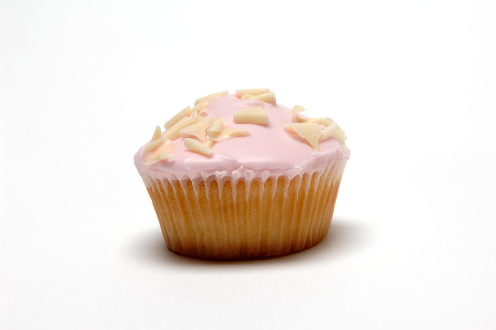 Single pink-iced cupcake covered in white chocolate curls