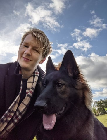 A picture of Alex and his 8-month-old German Shepherd, Wanda. The picture is taken on a sunny British afternoon. Wanda has a red mane, big brown eyes, and her tongue is lolling in the wind, Alex is looking goofily at the camera.