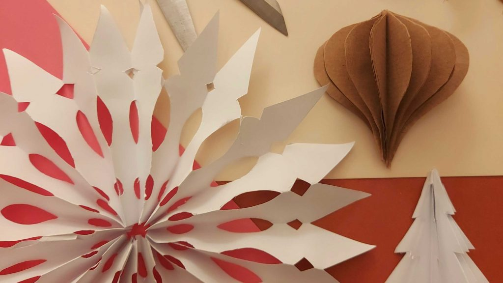 A snowflake made out of paper on a table next to a 3D Christmas tree made out of paper