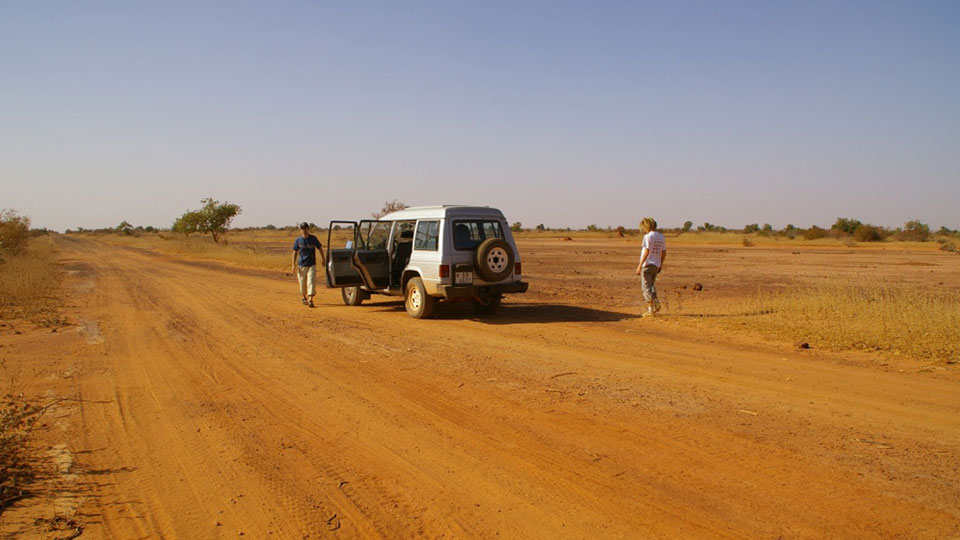 Two people stood outside a car on a dessert track
