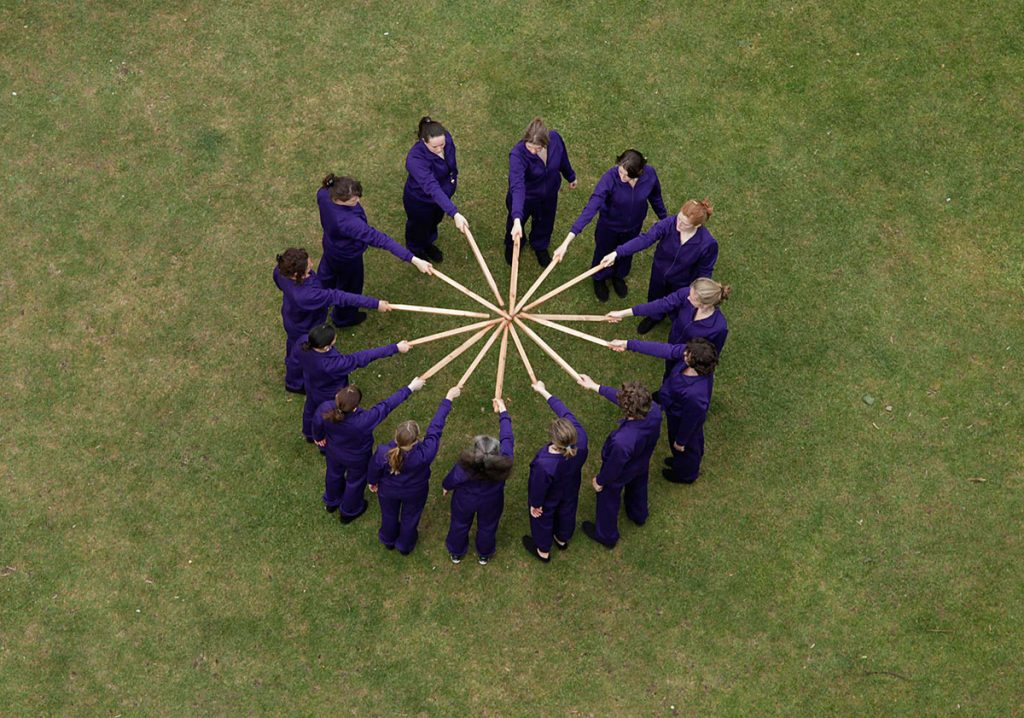 People dressed in purple standing in a circle holding sticks