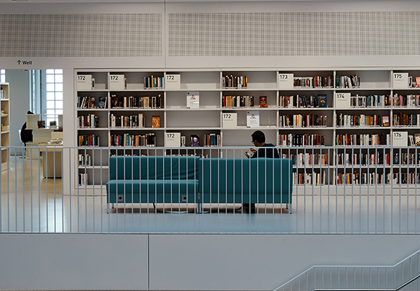 the inside of a brightlky lit library with a person sitting reading on a sofa