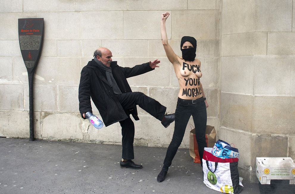 man kicking muslim topless woman